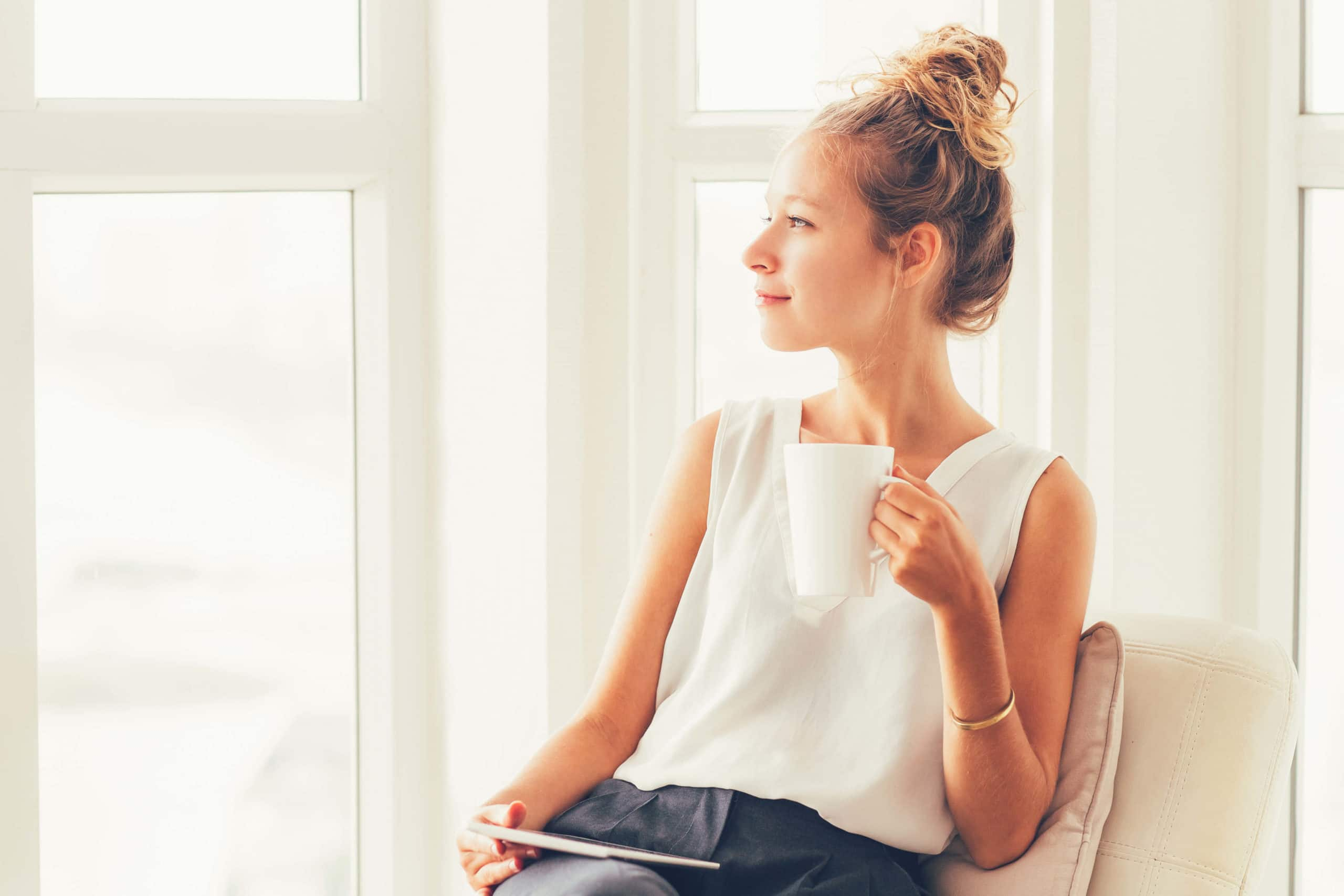 smiling woman sitting on cozy chair with mug near large windows