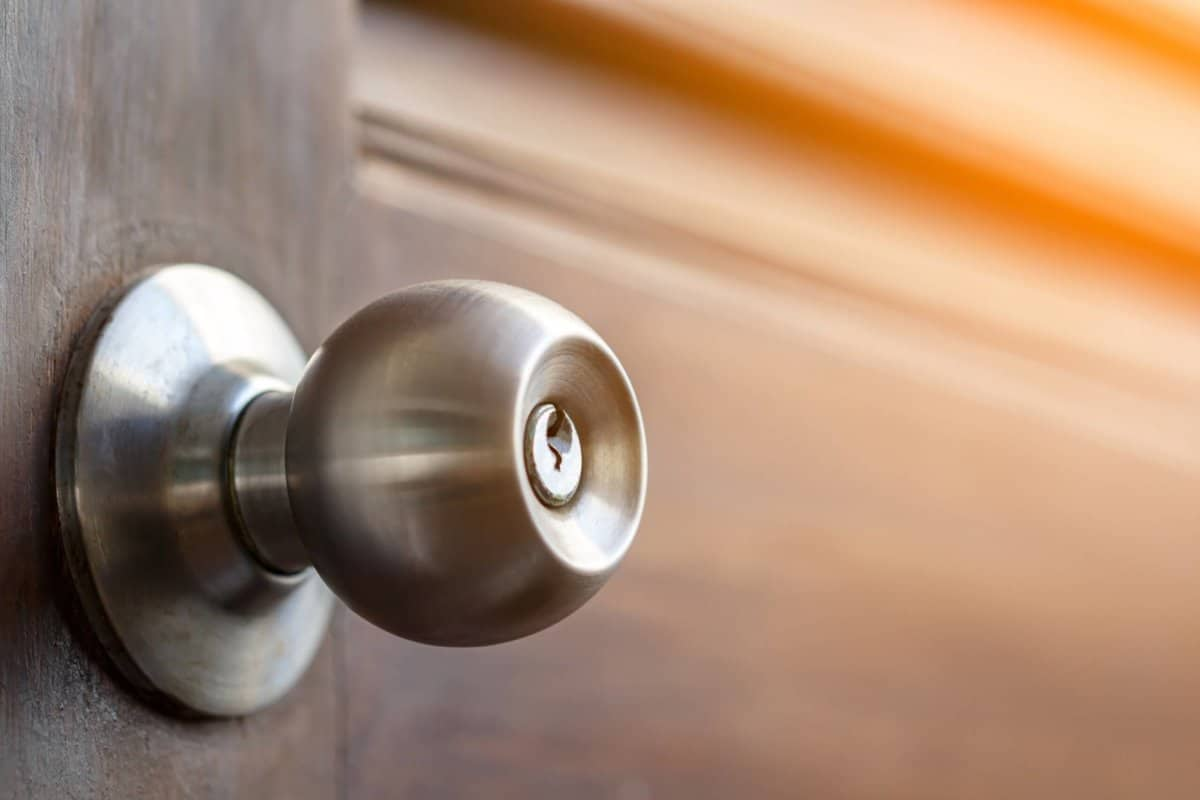 stainless door knob and keyhole on old wooden door with sunlight effect, shallow depth of field